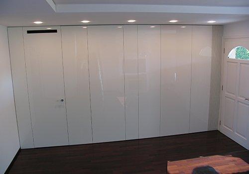 una stanza con  un armadio lungo e una porta di color bianco