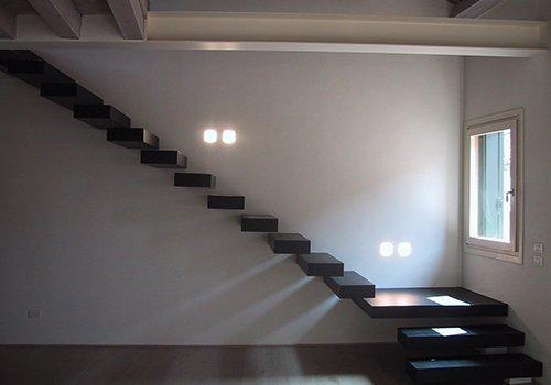 delle scale in legno di color nero a muro