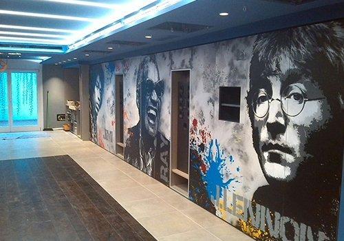 un muro dipinto di grigio con le immagini disegnate di John Lennon, Ray Charles e Jimi Hendrix