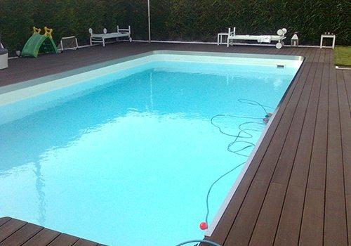 una piscina con un pavimento in parquet attorno