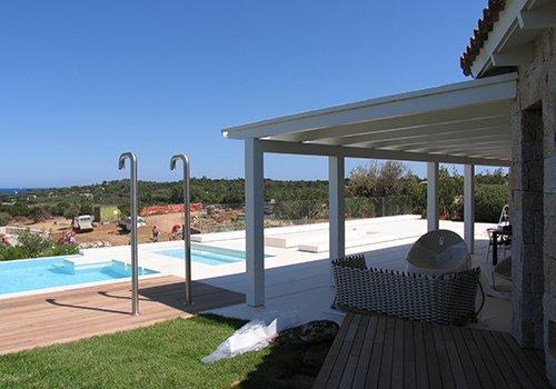 una tettoia di una villa sorretta da delle travi in legno e vista di una piscina