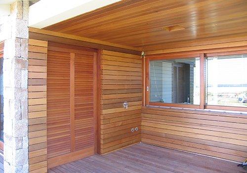 una porta finestra e pareti  in legno all'esterno di una casa