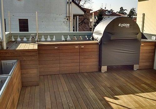 dei mobili in legno all'esterno e un forno coperto da un telo