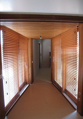un corridoio con delle finestre sui lati e delle tende oscuranti