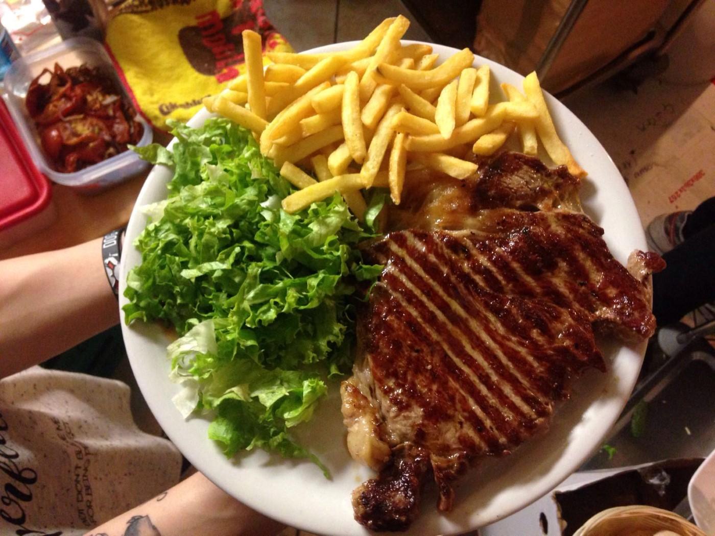 piatto con carne alla piastra, patatine fritte ed insalata