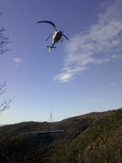 un elicottero che trasporta dei tubi di ferro
