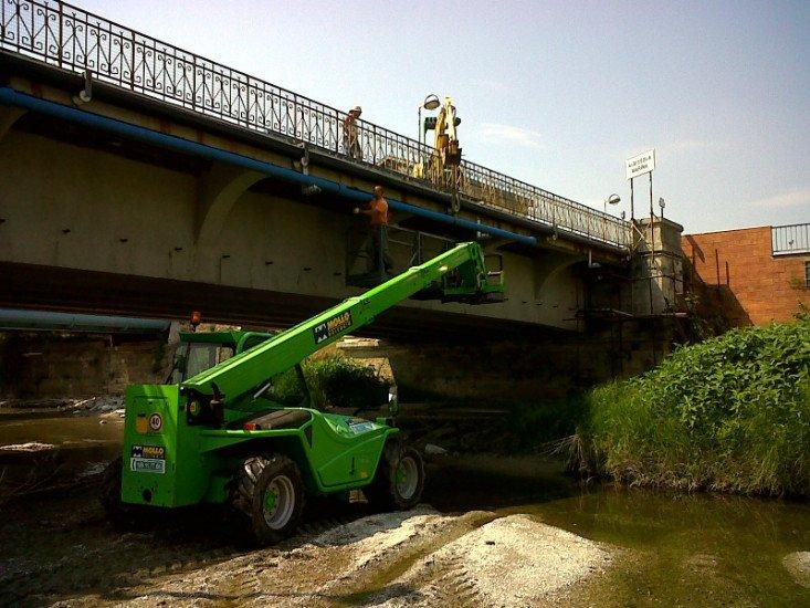 un mezzo da lavoro verde vicino a un corso d'acqua con sopra un ponte