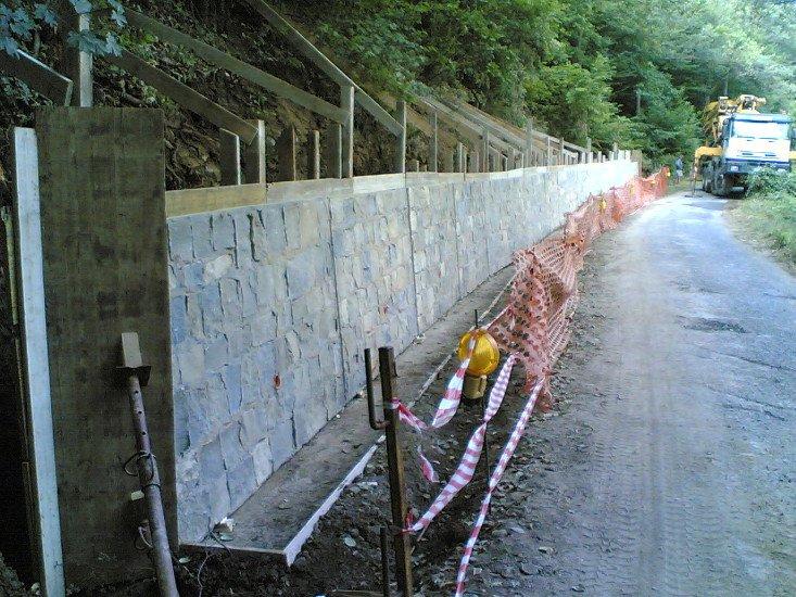 una rete rossa di plastica che indica lavori in corso e un muro di pietra su un lato della strada