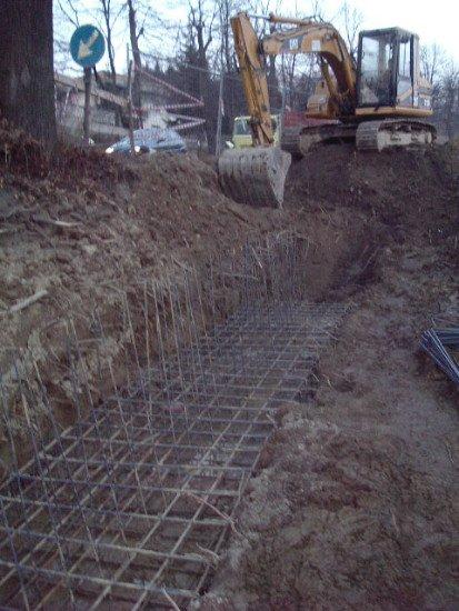 una scavatrice che scava in un terreno e vista delle fondamenta in ferro