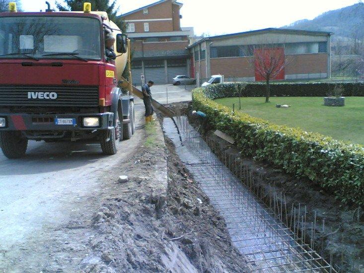 un camion rosso e sulla sinistra uno scavo con delle fondamenta