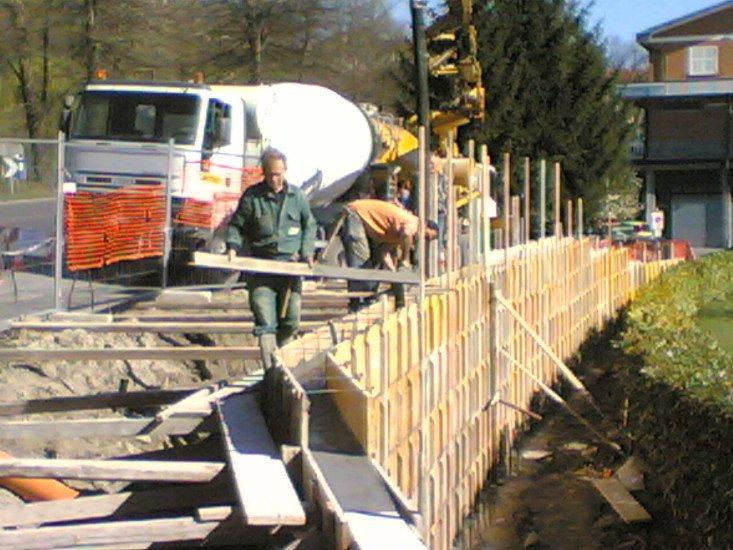 degli operai al lavoro con delle assi di legno e una betoniera