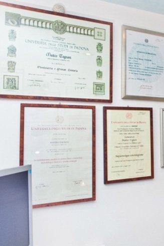 dei certificati e dei riconoscimenti in cornice appesi al muro