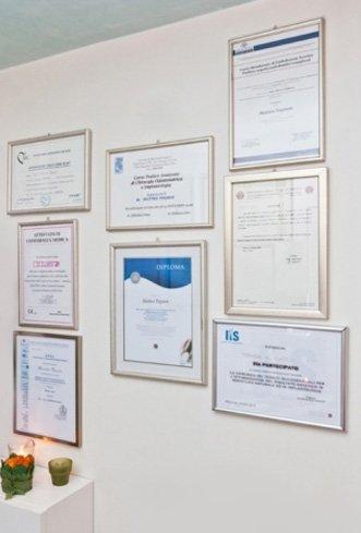 dei certificati appesi al muro