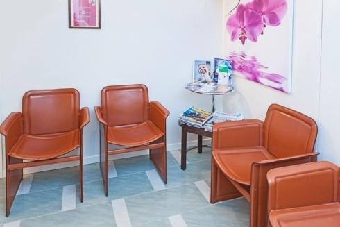 una saletta d'attesa con tre sedie in pelle marrone e un tavolino con sopra delle riviste