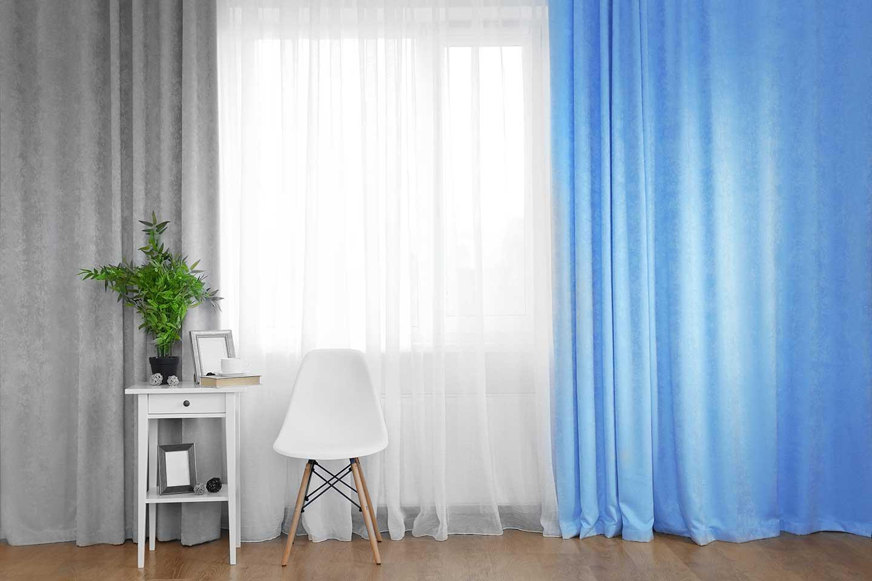 luce dietro delle tende grigie bianche e azzurre
