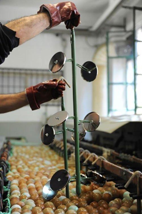 un uomo sta lavorando con un supporto in ferro verde con dei dischi in acciaio