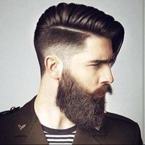 un ragazzo con capelli rasati ai lati, sopra la riga da parte e la barba