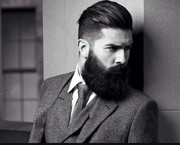 un ragazzo con capelli rasati ai lati, sopra la riga da parte e la barba folta