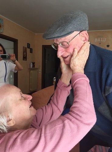 una signora anziana con le mani sul viso di un altro signore con una coppola
