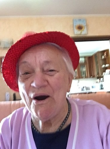 una signora anziana sorridente con un cappellino rosso