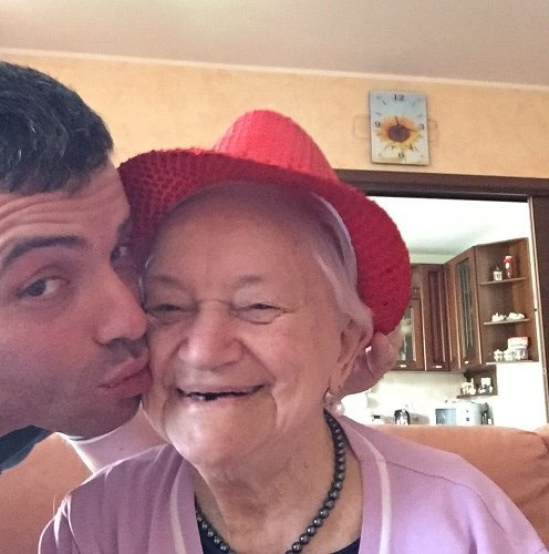 un ragazzo che bacia sulla guancia una signora anziana con un cappellino rosso