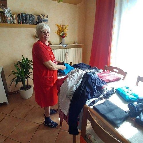 una signora anziana in piedi vicino a un tavolo con sopra dei vestiti
