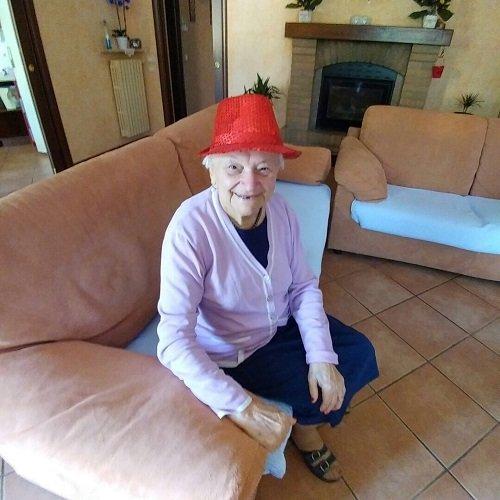 una signora anziana sorridente seduta sul divano con un cappellino rosso