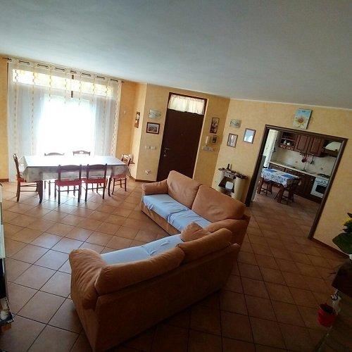 un salotto con due divani arancioni  e un tavolo con le sedie