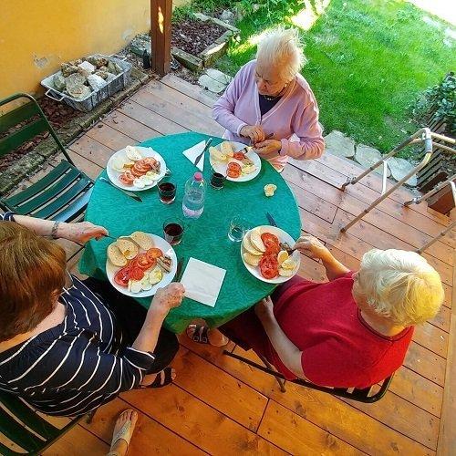 tre signore sedute a un tavolo mentre mangiano
