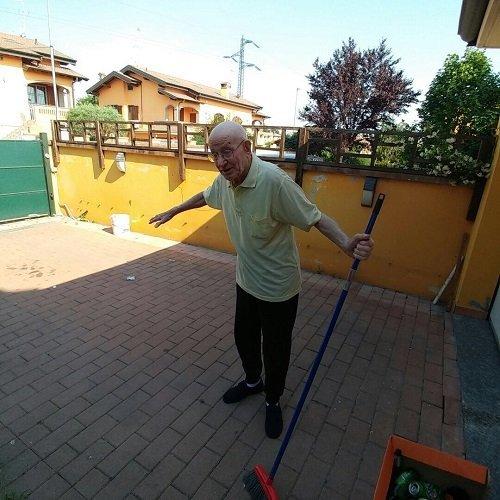 un signore anziano che gesticola con una scopa in mano