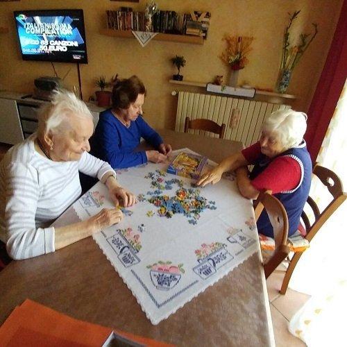delle signore sedute a un tavolo  che fanno un puzzle