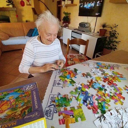 una signora anziana intenta a fare un puzzle