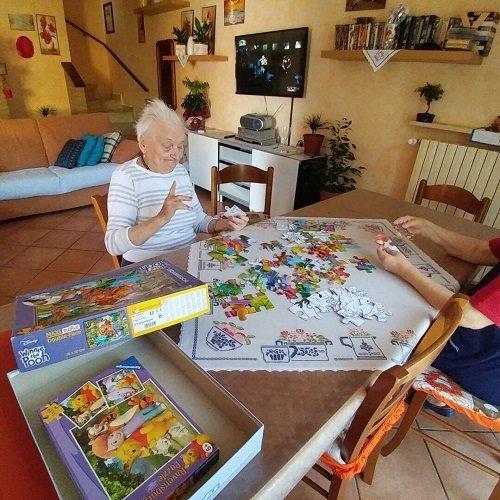 una signora anziana seduta che fa un puzzle e di fronte un'altra