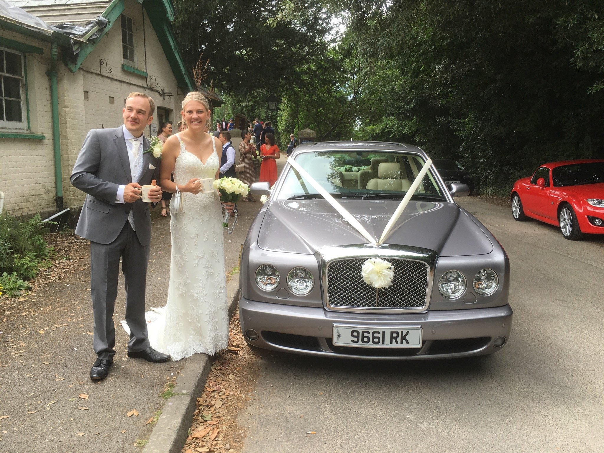 Couple posing with their wedding car
