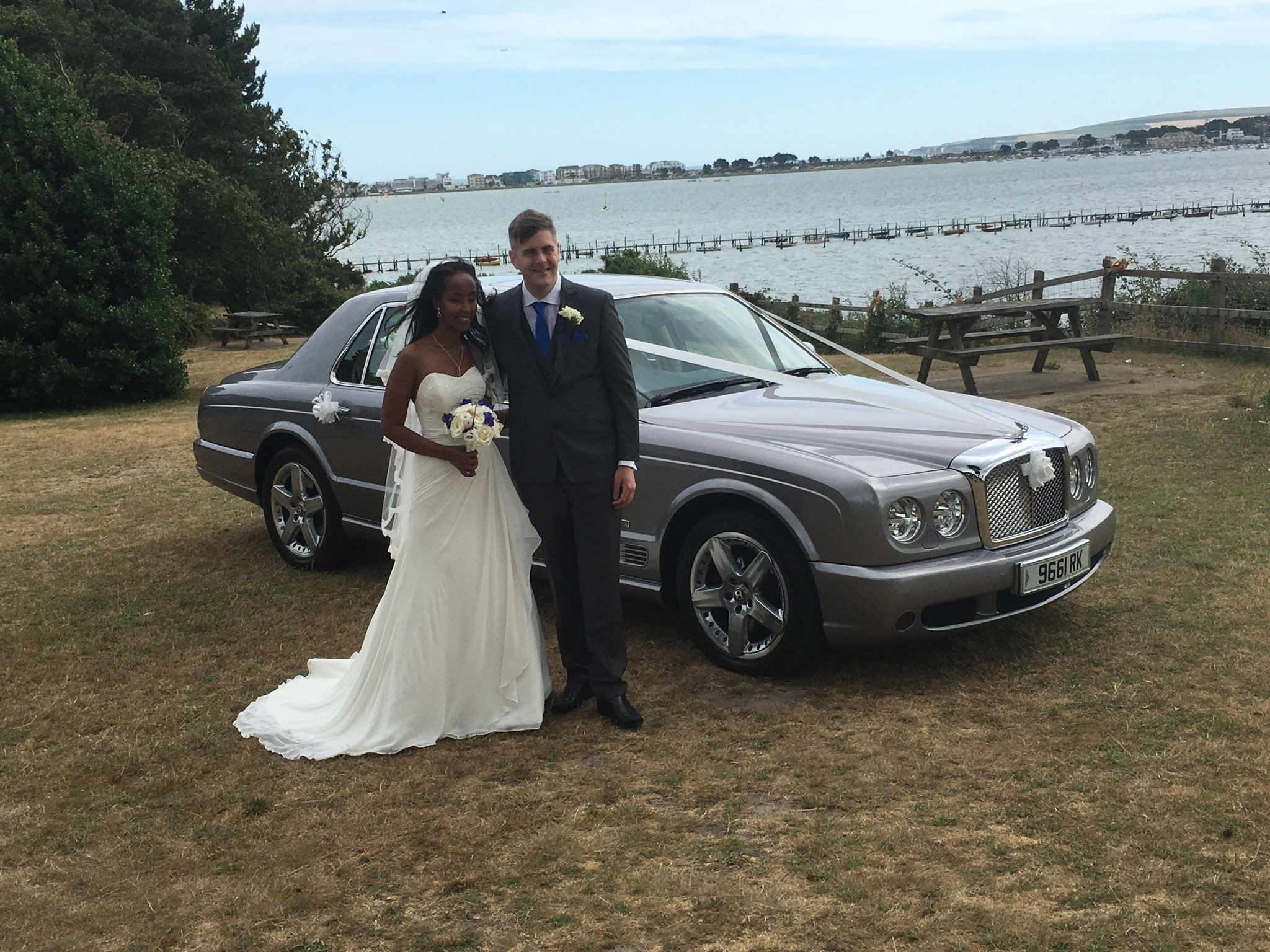 Couple posing with their rented wedding car