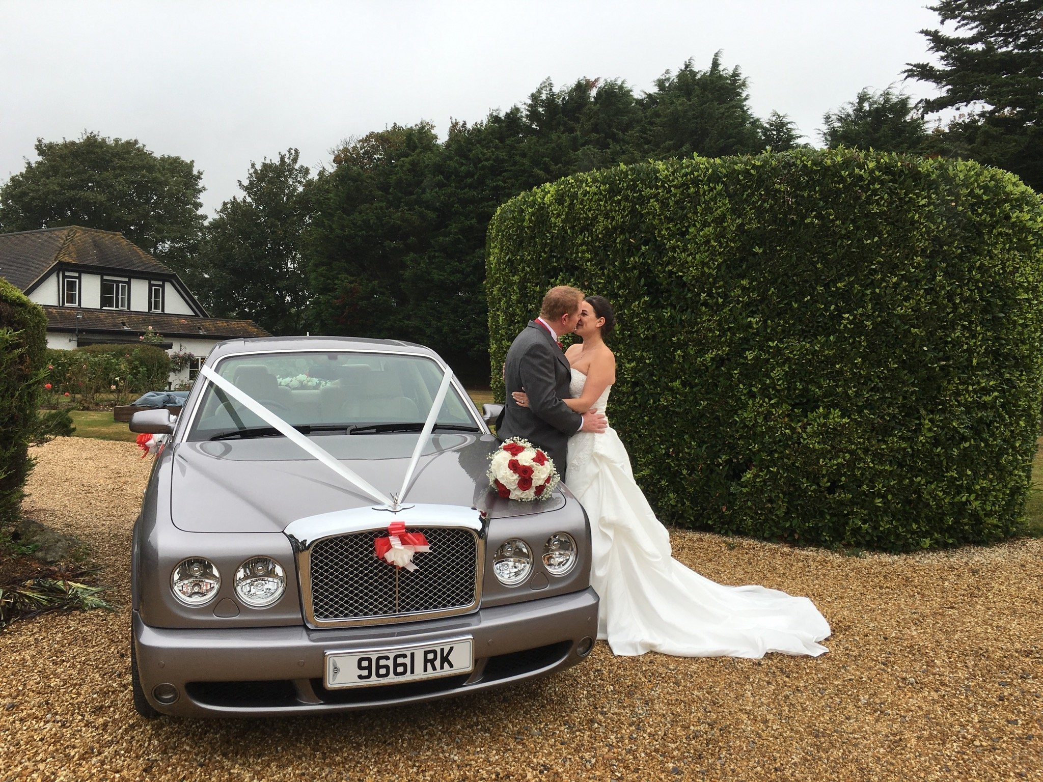 Couple posing next to their wedding car