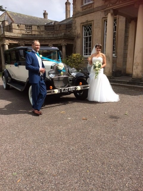 Newly wedded couple pose with the car