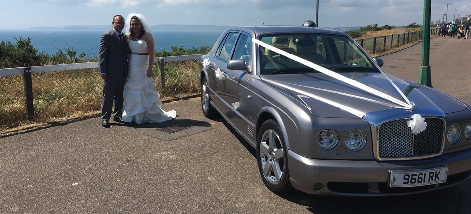 Couple posing infront of their wedding car