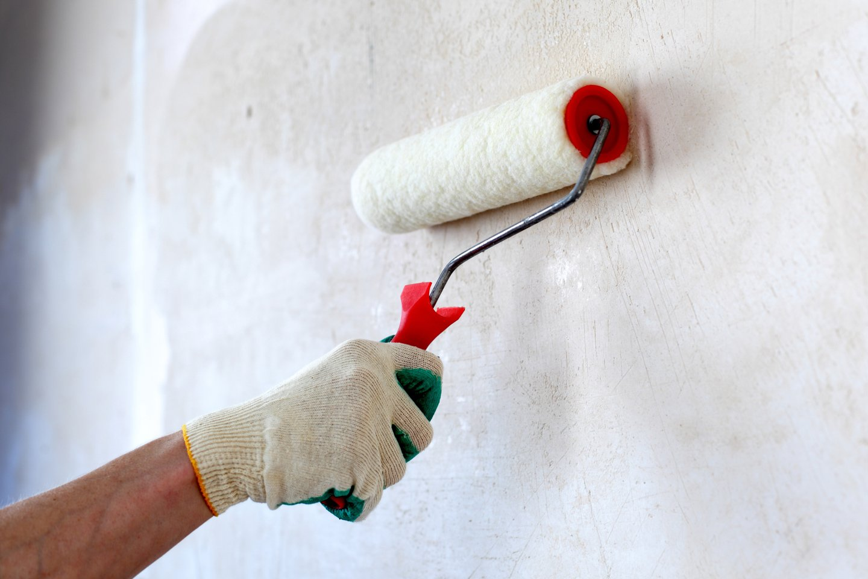 pittore imbianca parete con rullo