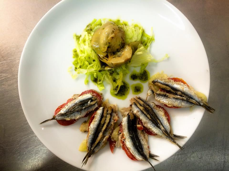 un piatto con delle sardine,verdura e altro