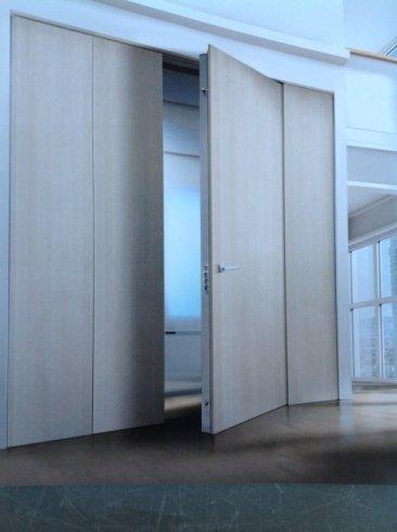 una porta in legno beige e accanto delle ante