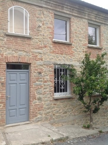 un portone grigio di un edificio in pietra e con mattoni a vista