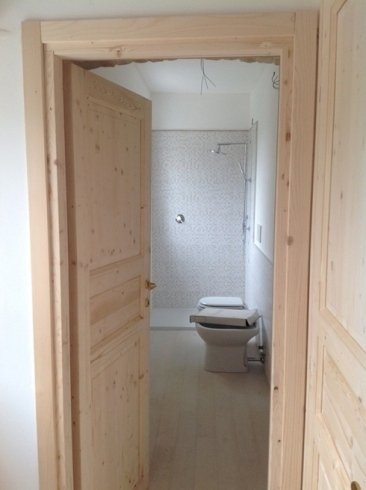 una porta in legno e vista di un bagno