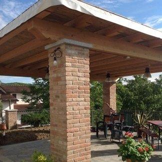 una copertura in legno con colonne di mattoni a vista