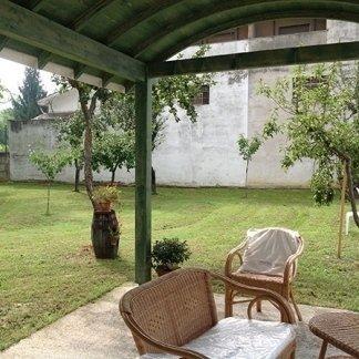 delle sedie in paglia sotto una copertura verde in un giardino