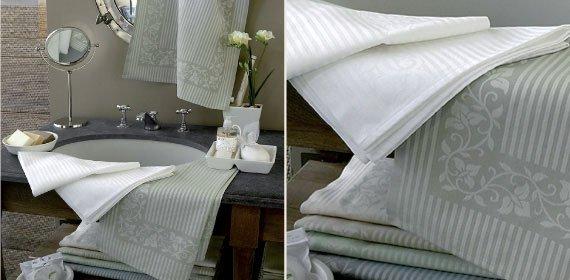 degli asciugamani di color bianco e verde  in un bagno