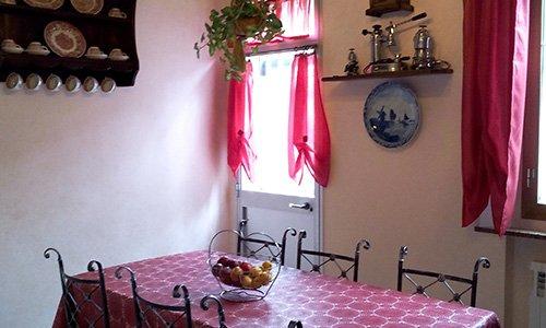 cucina con pareti bianche e beige, tavolo con tovaglia rossa