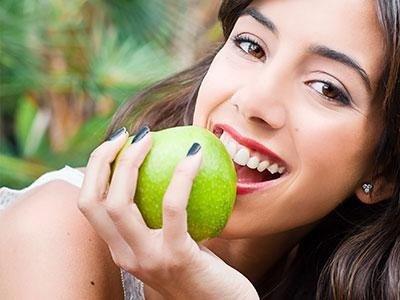 giovane donna con il dente sano mentre morde la mela verde