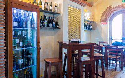 Interno del locale con sgabelli, tavolino e bottiglie di vino su mensole
