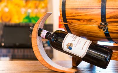una bottiglia di vino in un portabottiglie obliquo di fianco a una botte di legno